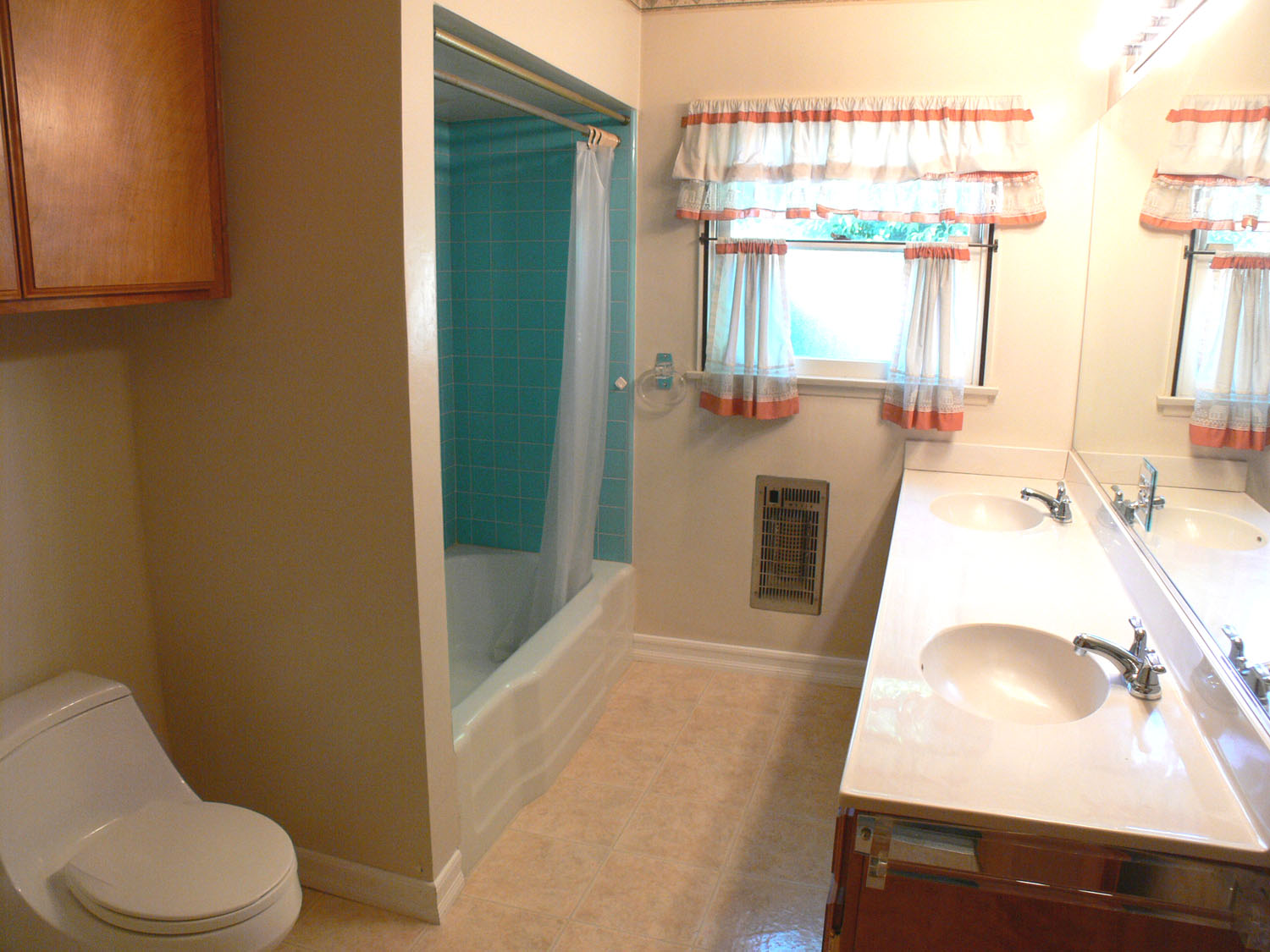 One of the three bathrooms. This one has double sinks, newer low-flow toilet, and impeccable tile in the shower/tub enclosure!