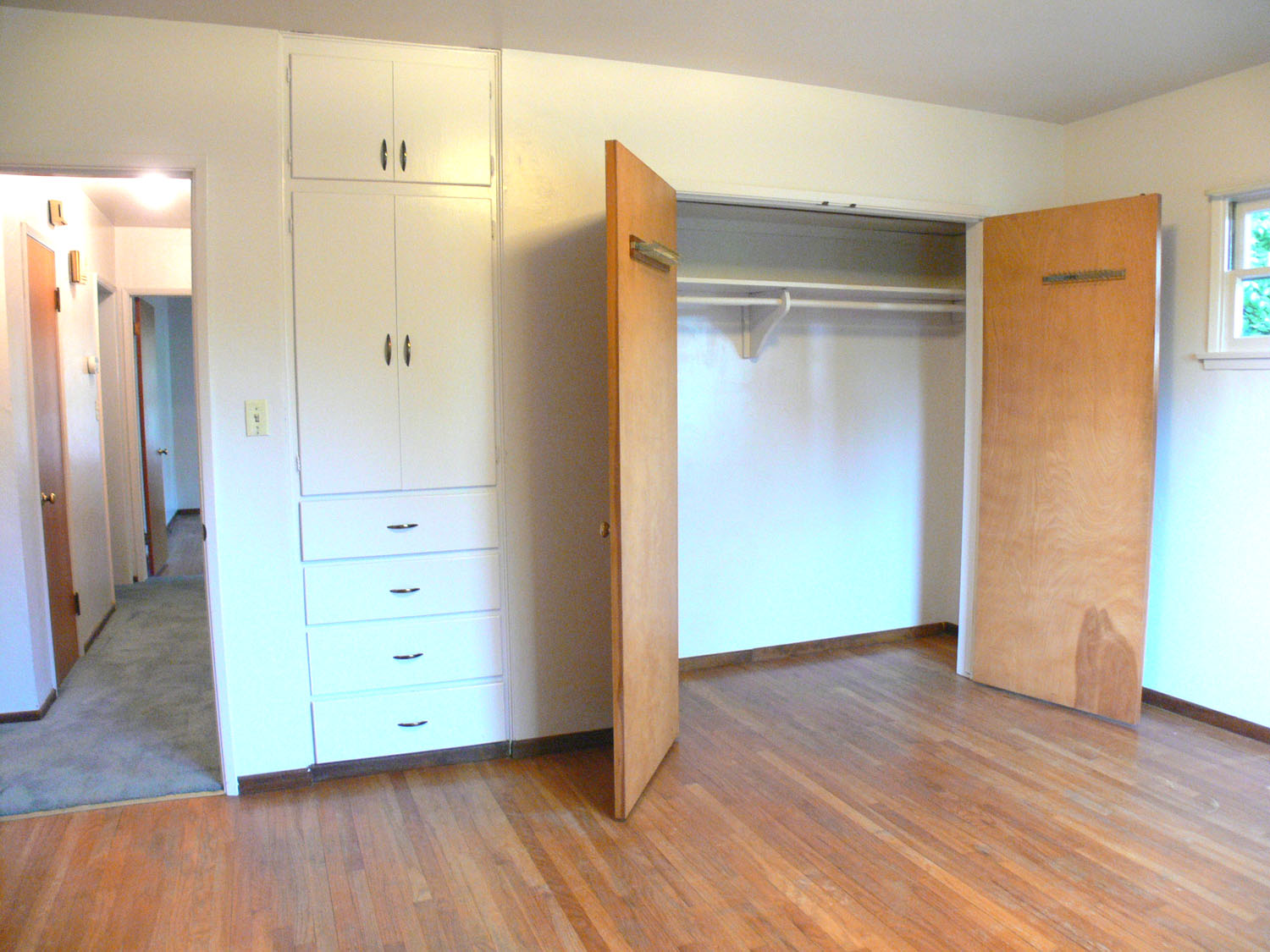 Each of the three bedrooms with hardwood floors hav a large closet and a built-in dresser like the one to the left of this closet!