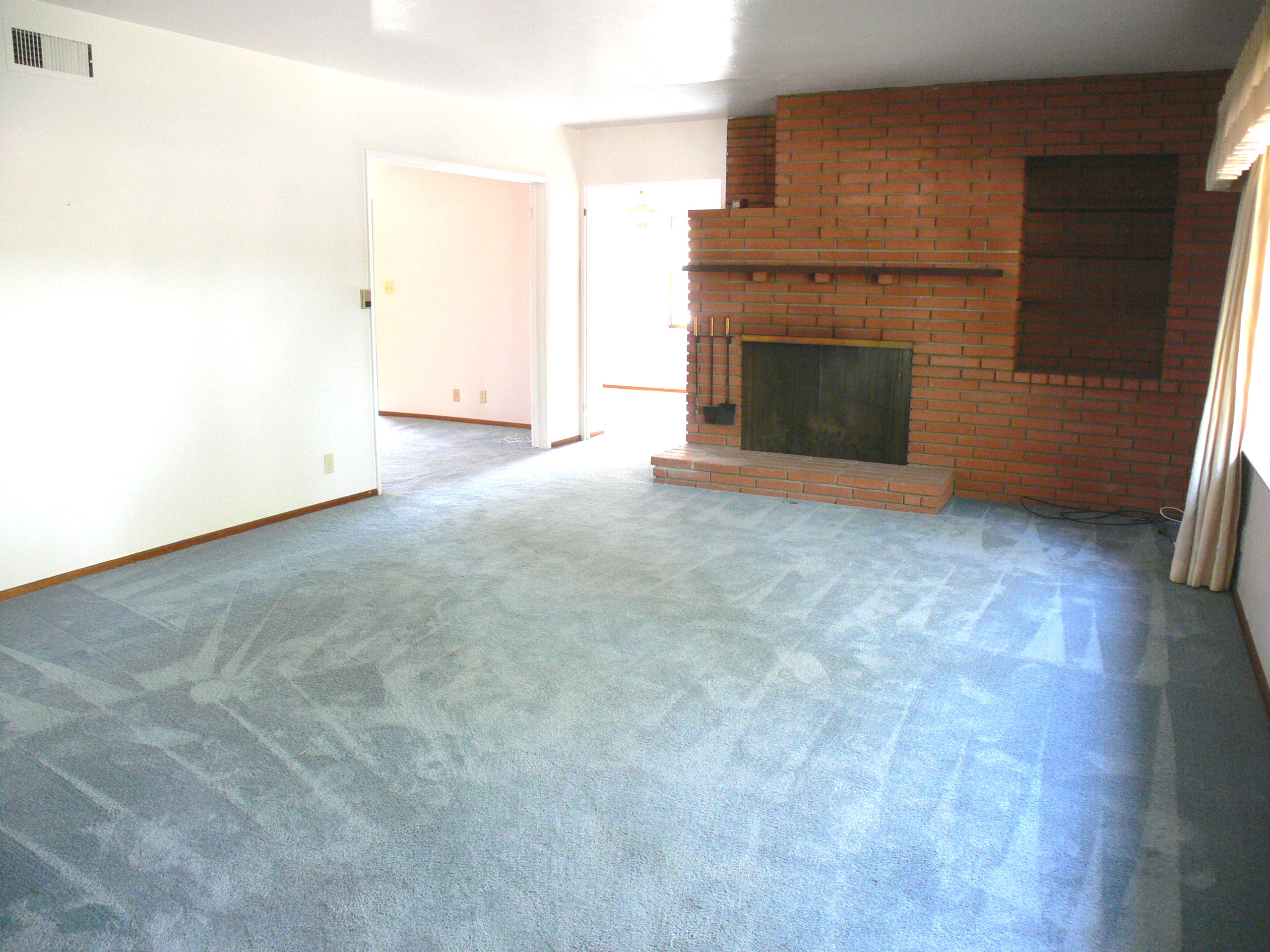 View of living room as you walk throught the front door. Keep in mind, the hardwood floors under this carpet are GORGEOUS! Note the built-in shelving next to the brick fireplace!