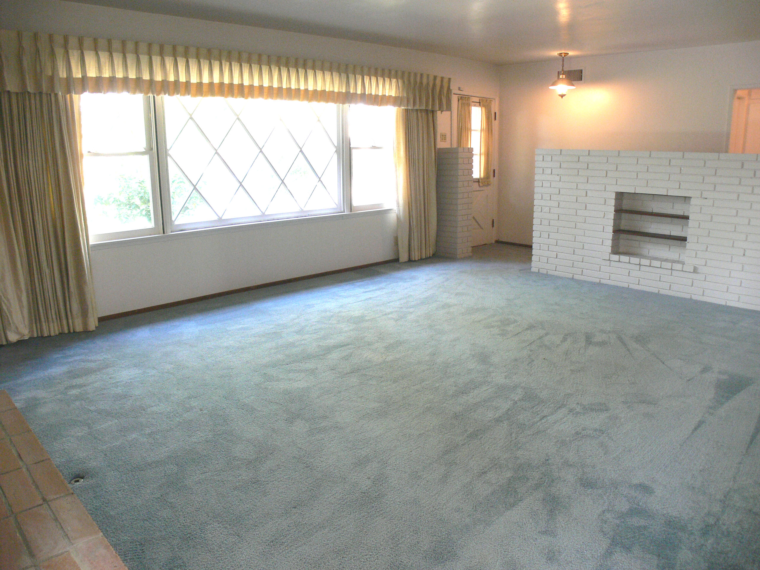 Massive living room with gorgeous hardwood floors under carpet. This room will look even larger with the hardwood floors exposed!