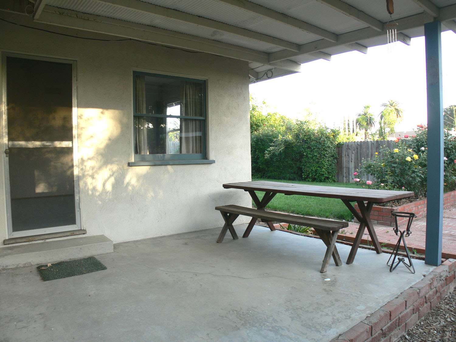 Side patio that is covered, and overlooks the beautiful rose bushes.