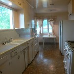 Eat-in kitchen with original built-in ironing board, antique stove, and original counter tops and cabinetry.