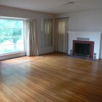 Large living room with original hardwood floors, fireplace and lots of windows!