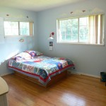 Bedroom (main level) with ample closet space and beautiful hardwood floors.