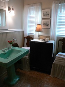 Very nice hall bathroom with original 1930's-era pedestal sink and toilet. There is also a tub and shower to the right.