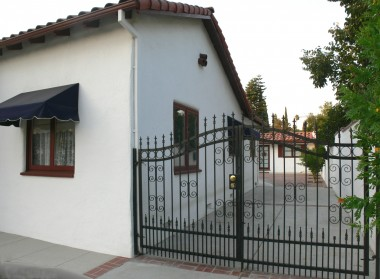 Side of house and long driveway (with small RV/boat parking) complemented by handsome wrought iron gate.