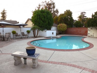 View of low-maintenance backyard with flagstone patio area for table, umbrella and chairs.