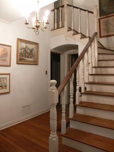 Entry with winding stairway and hardwood floors.